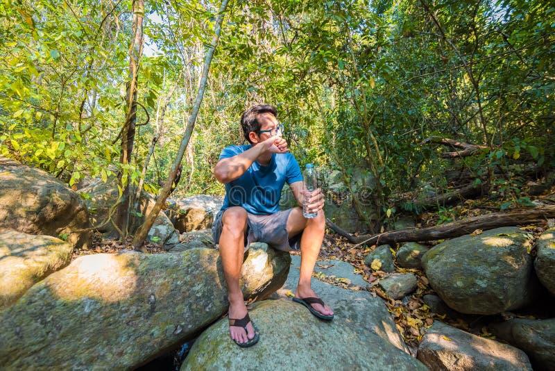 Un'acqua potabile dell'uomo dalla bottiglia di plastica sopra nella natura pura della foresta si rilassa il concetto fotografia stock libera da diritti