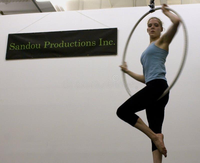 Un acrobate féminin balance d'un cercle aérien photos stock