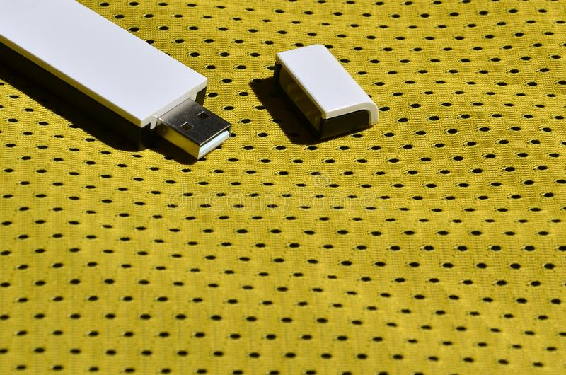 Un adaptador moderno del portable USB Wi-Fi se coloca en la ropa de deportes amarilla hecha de fibe del nilón del poliéster fotos de archivo libres de regalías