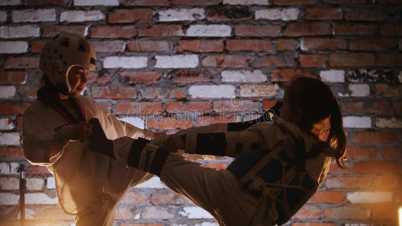 Un addestramento di due bambine le loro abilità di karatè nello studio attacco fotografia stock libera da diritti