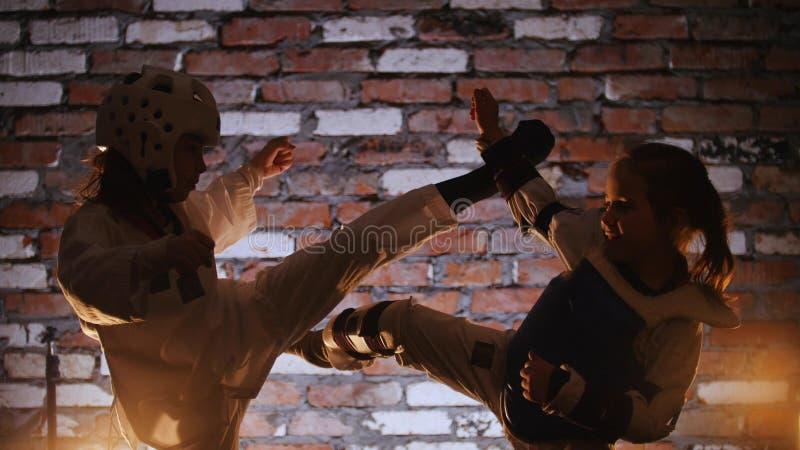 Un addestramento di due bambine le loro abilità di karatè nello studio immagine stock