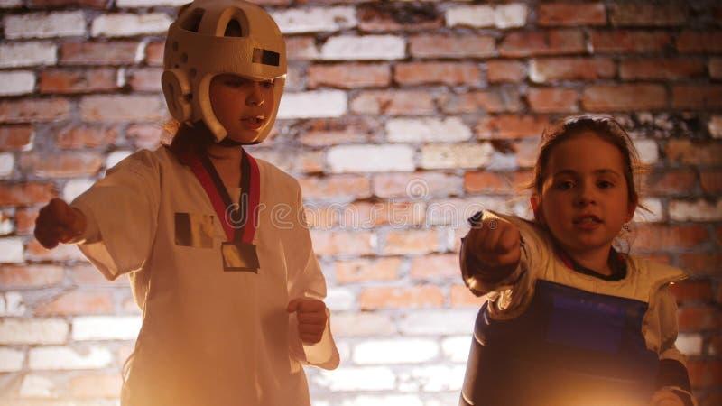 Un addestramento di due bambine le loro abilità di karatè nello studio Muro di mattoni su un fondo fotografia stock libera da diritti