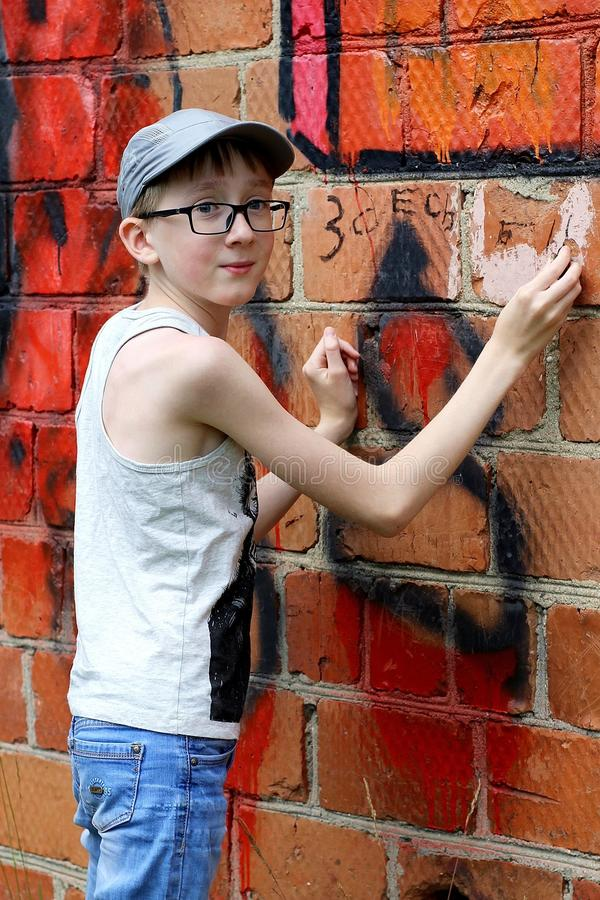Un adolescent a écrit avec du charbon sur le mur rouge des briques images libres de droits