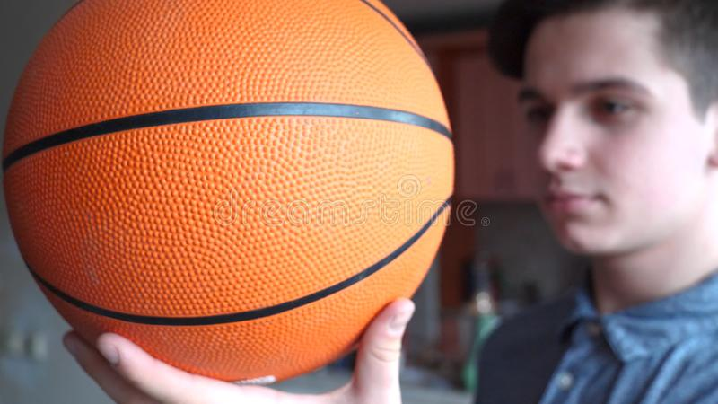 Un adolescent bel de garçon tient un basketballl image stock