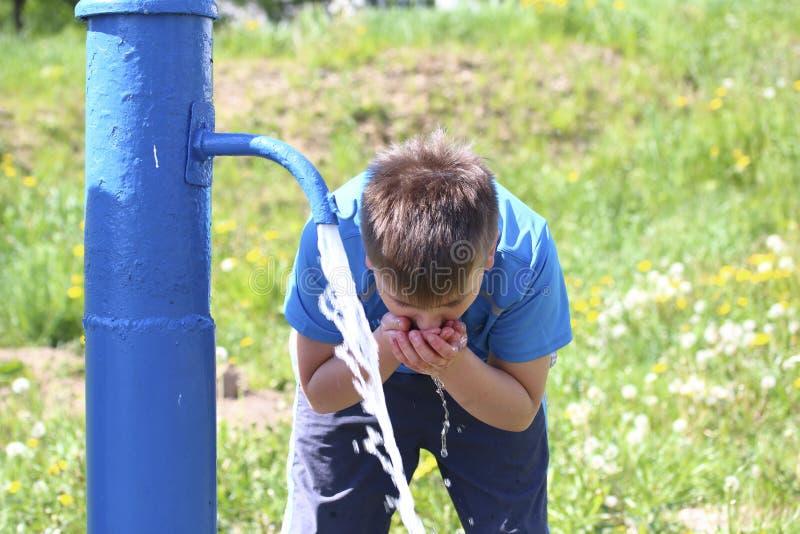 Un adolescent boit l'eau d'une colonne publique sur la rue Il écope l'eau avec ses mains image stock