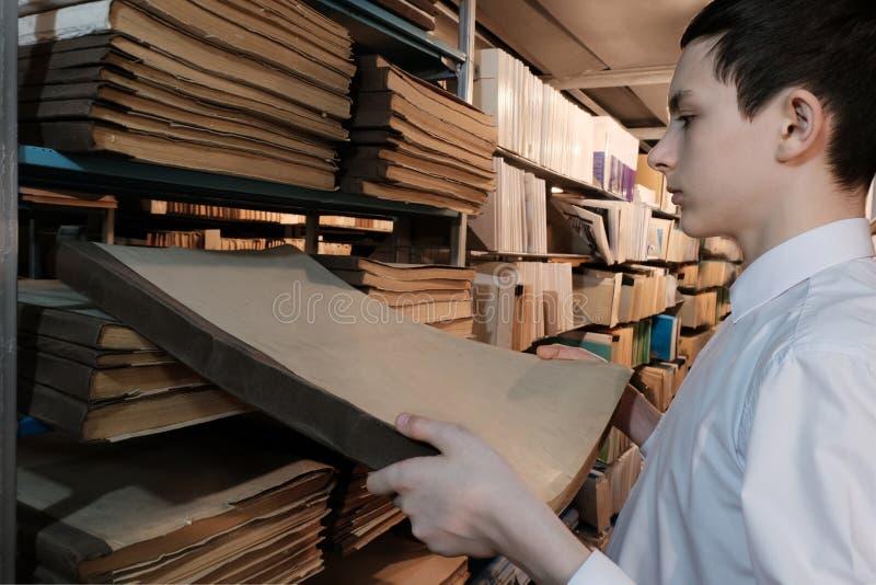 Un adolescent dans une chemise blanche retire un vieux livre d'une étagère Un étudiant dans la bibliothèque ou dans la salle d'ar images libres de droits