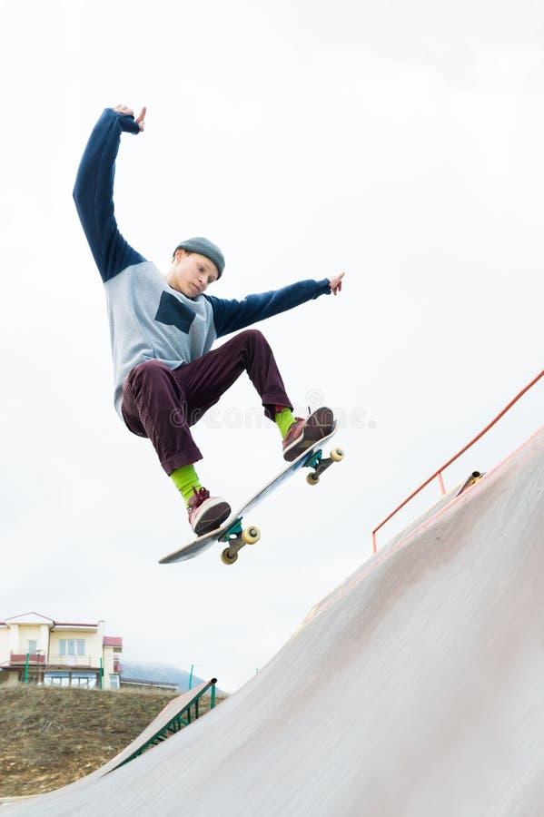 Un adolescent de planchiste dans un chapeau fait un tour avec un saut sur la rampe Un planchiste vole dans le ciel photos libres de droits
