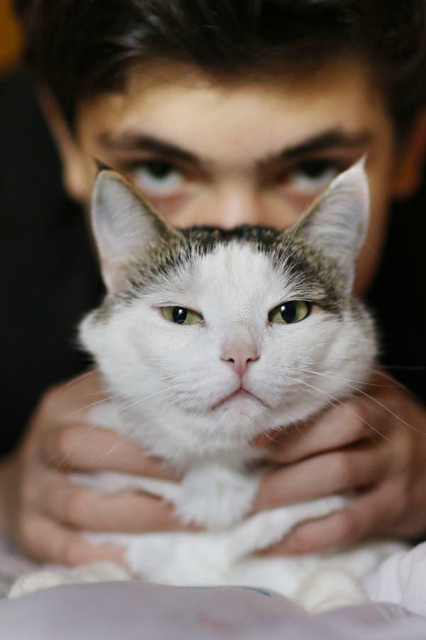 Un adolescent dort avec un chat dans son lit photos stock