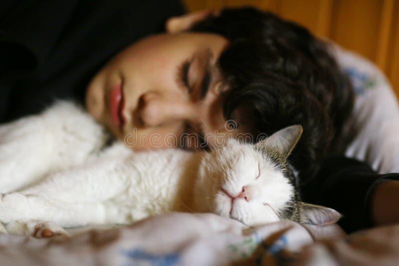 Un adolescent dort avec un chat dans son lit photo stock