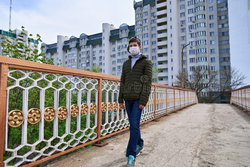 Un adolescent marche dans la rue pendant la journée, une promenade piétonne et des tours avec des appartements, un quartier résid image libre de droits