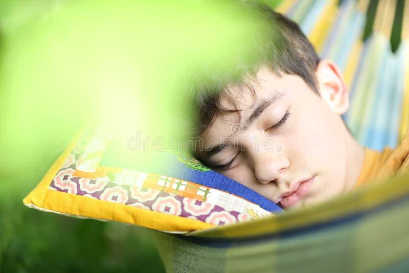 Un adolescent se reposant avec un livre dans un hamac sur un jardin d'été verdoyant images stock