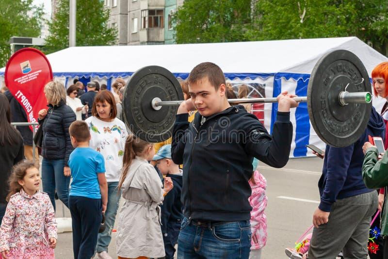 Un adolescent sur le festival soulève la barre de l'haltérophilie image libre de droits