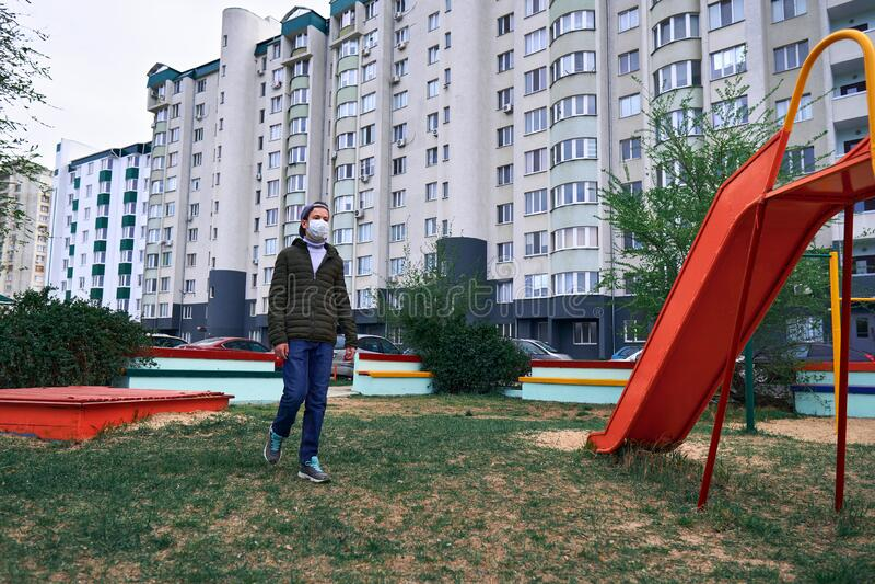 Un adolescent traverse l'aire de jeux près de gratte-ciel avec des appartements, une zone résidentielle, un masque médical sur le photos stock