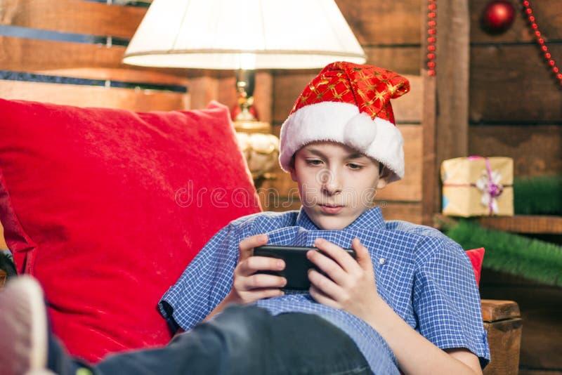 Un adolescente in un cappello di Santa Claus, in jeans, in una camicia blu, sta trovandosi su una sedia con i cuscini rossi ed es immagine stock