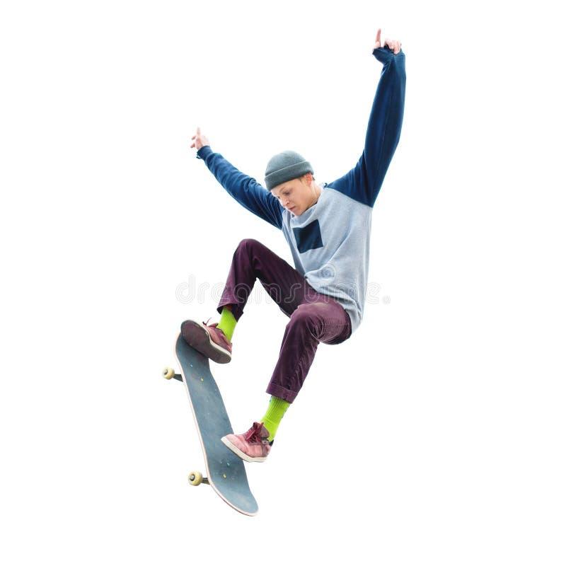 Un adolescente in un cappello ed in una maglietta felpata che saltano con un pattino fa un trucco su un fondo bianco isolato Il t fotografia stock