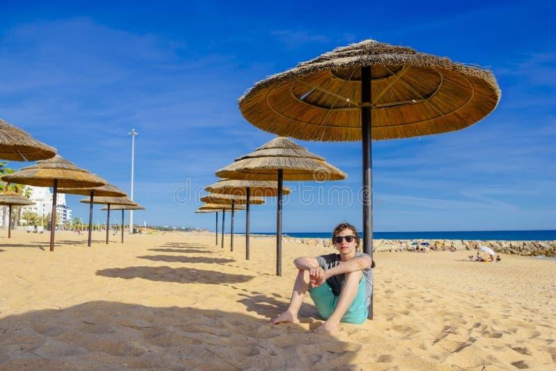Un adolescente che si siede sotto l'ombrello a lamella sulla spiaggia fotografia stock