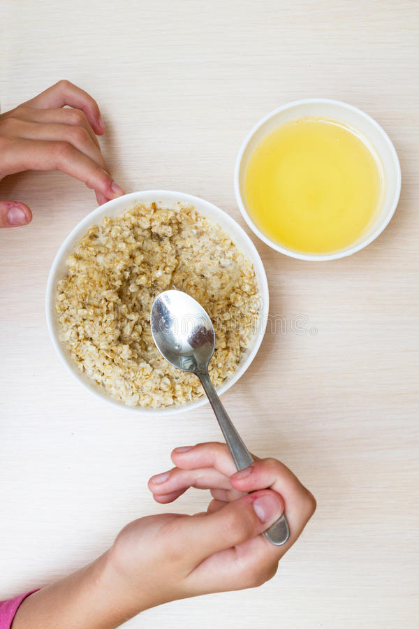 Un adolescente come la harina de avena con la miel imagen de archivo