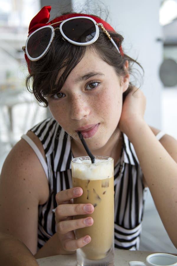 Un adolescente con le bevande graziose delle lentiggini ghiaccia il caffè in un caffè vicino alla finestra fotografie stock