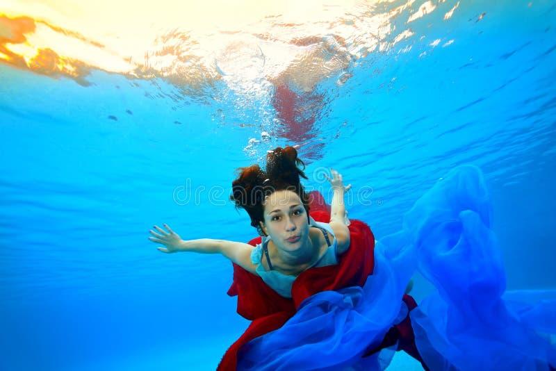 Un adolescente con un panno rosso e blu si tuffa underwater sul fondo dello stagno contro lo sfondo delle luci intense fotografie stock