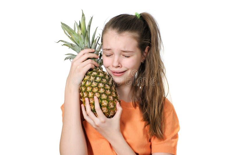 Un adolescente con un'allergia abbraccia un ananas e grida immagine stock