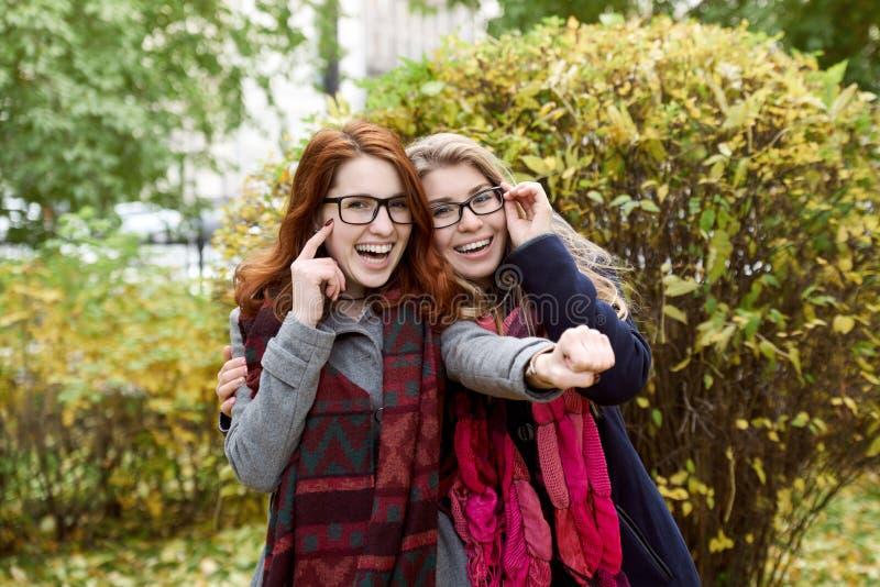 Un adolescente di due amiche che cammina nel parco e nel Hamming per una p fotografie stock