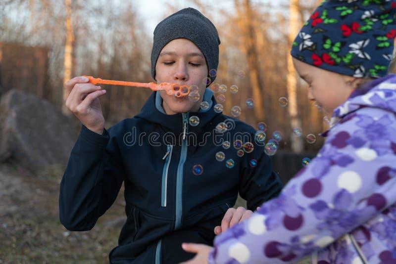 Un adolescente en burbujas que soplan de una chaqueta azul y de un sombrero gris y de una muchacha en el aire abierto Retrato del fotografía de archivo