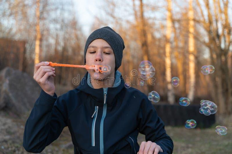 Un adolescente en una chaqueta azul y un sombrero gris está soplando burbujas en el aire abierto Retrato del ` s de los ni?os imagen de archivo libre de regalías