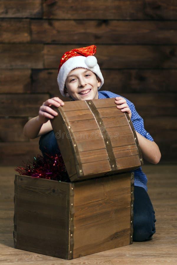 Un adolescente europeo típico mira en la cámara y ríe cuando él abre un pecho de madera con los ornamentos de la Navidad Foto ver imagen de archivo