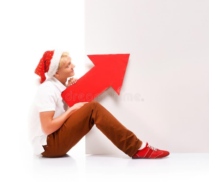 Un adolescente feliz en un sombrero de la Navidad que sostiene una flecha roja imagenes de archivo