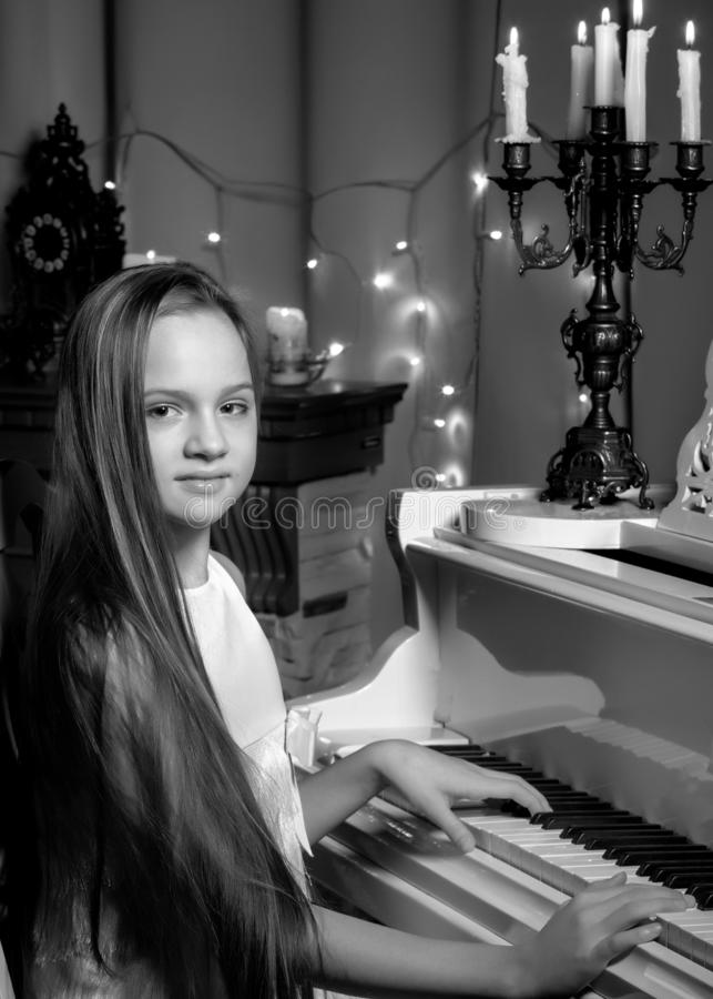 Un adolescente gioca un piano su una notte di Natale da lume di candela immagine stock