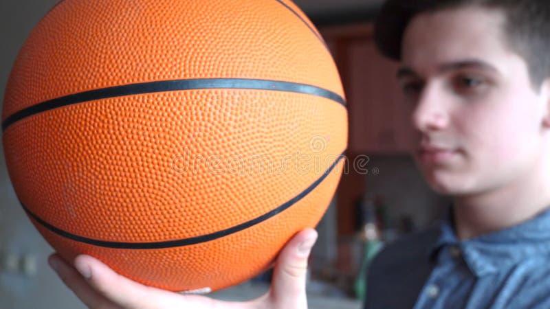 Un adolescente hermoso del muchacho está llevando a cabo un basketballl imagen de archivo