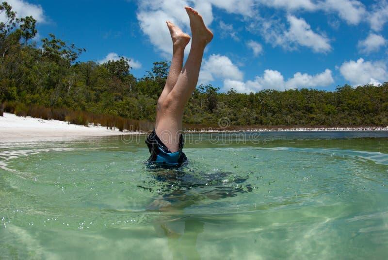 Un adolescente juega en las aguas cristalinas de Fraser Island fotografía de archivo