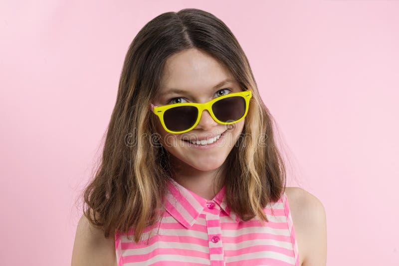 Un adolescente in occhiali da sole esamina la macchina fotografica e sorridere immagine stock libera da diritti