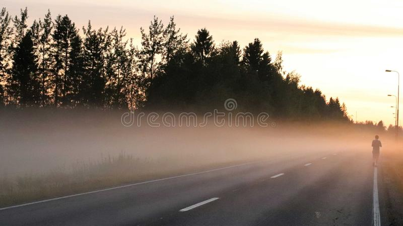 Un adolescente que camina solamente en un camino brumoso foto de archivo libre de regalías