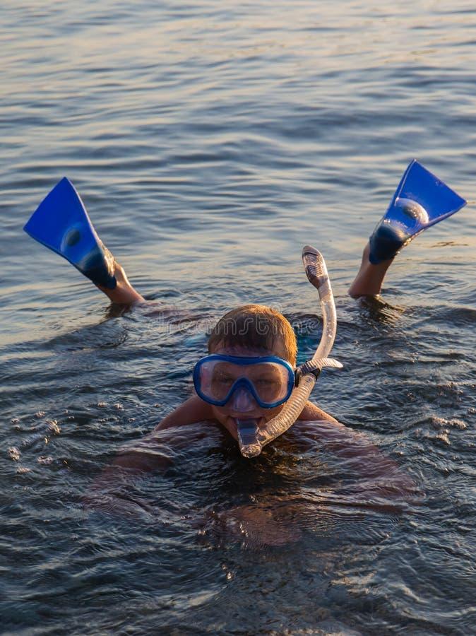 Un adolescente que lleva una máscara con el tubo para zambullirse y las aletas b imagen de archivo