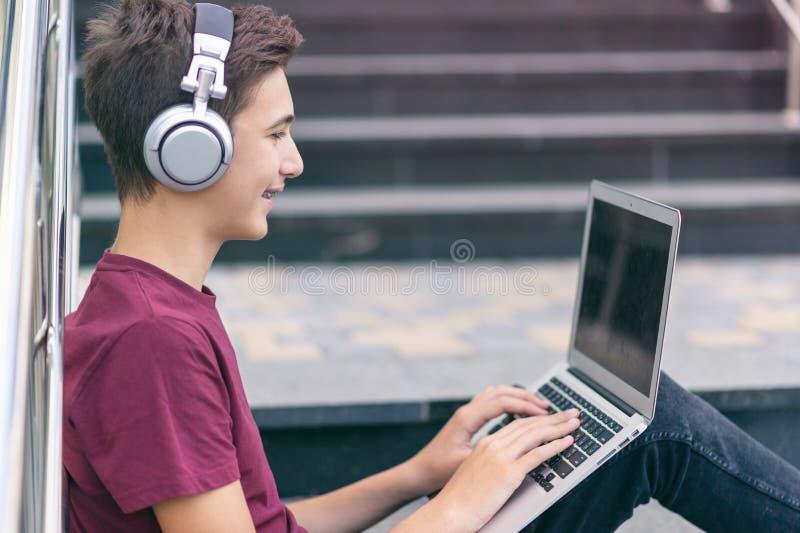 Un adolescente sorridente con un laptop per strada Giovane e bello lavora su un quaderno, all'aperto Un ragazzo allegro tiene il  fotografie stock