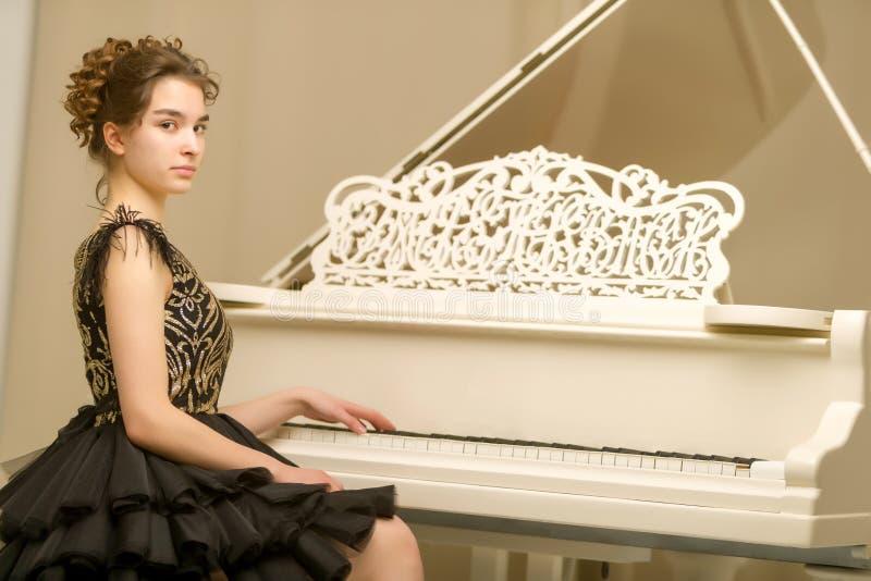 Un adolescente sta giocando su un pianoforte a coda bianco immagine stock