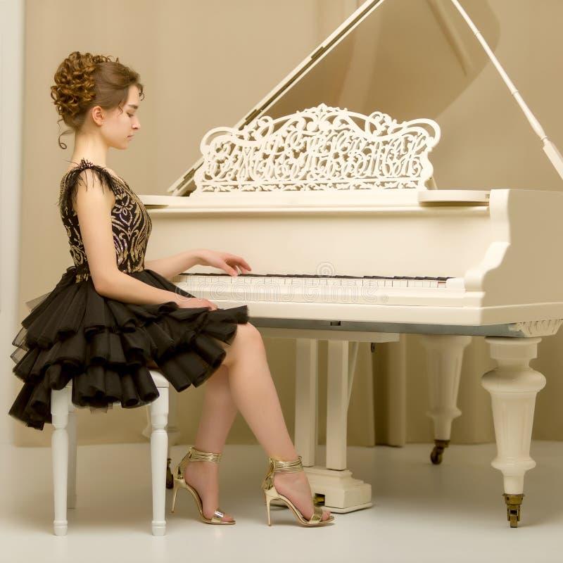 Un adolescente sta giocando su un pianoforte a coda bianco fotografie stock