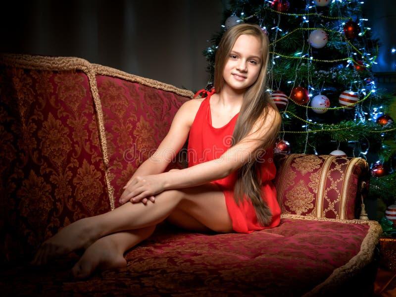 Un adolescente sta sedendosi vicino all'albero del nuovo anno fotografia stock libera da diritti