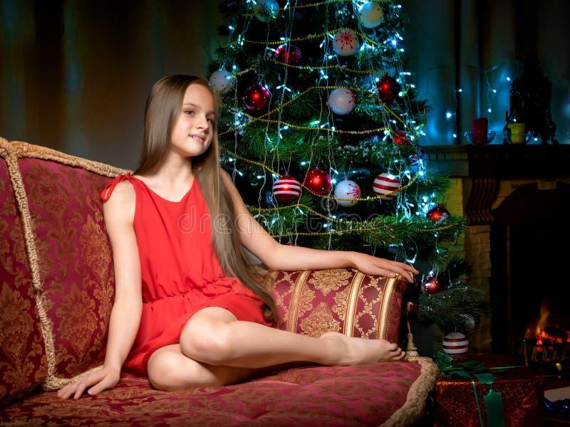 Un adolescente sta sedendosi vicino all'albero del nuovo anno fotografia stock