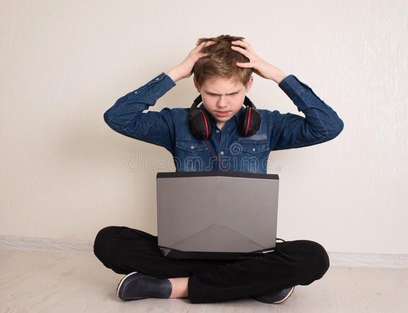 Un adolescente triste e preoccupato, con le mani sopra la testa dopo aver letto brutte notizie in linea con un portatile in ginoc fotografia stock