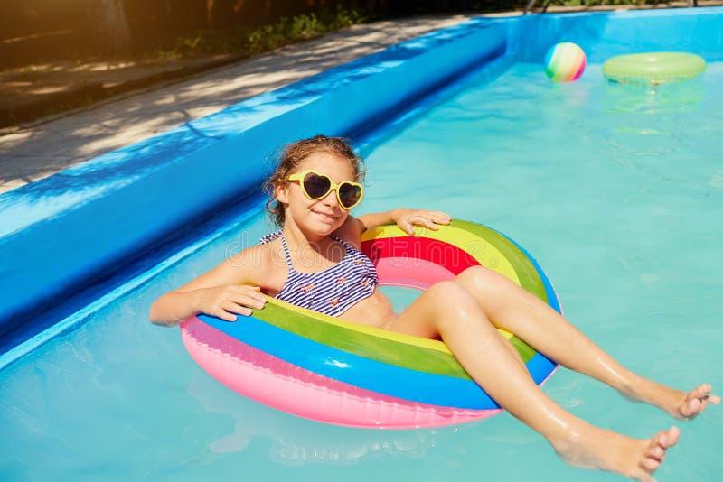 Un adolescente in un anello nell'acqua allo stagno fotografia stock