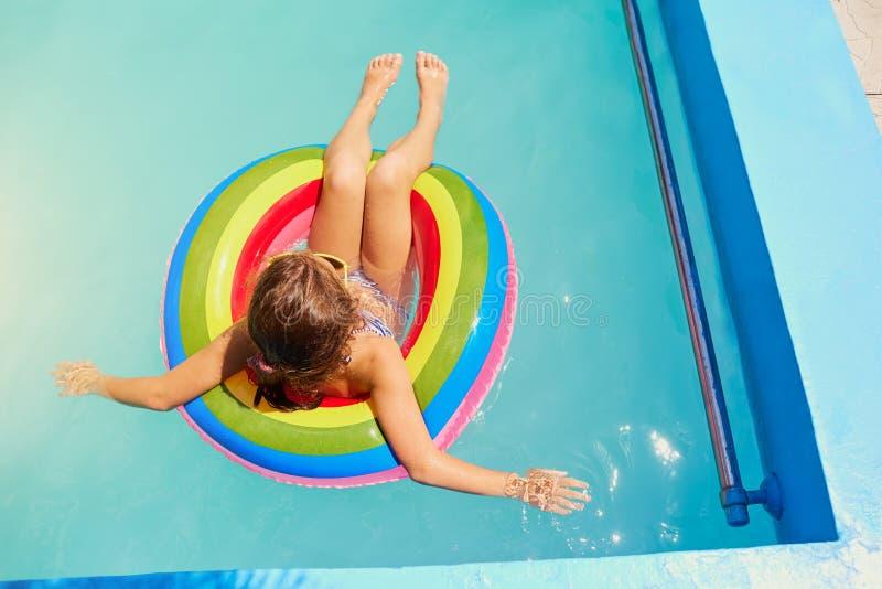 Un adolescente in un anello nell'acqua allo stagno fotografie stock