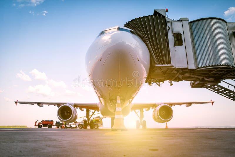 Un aeroplano bianco del passeggero sta al ponte d'imbarco ed è caricato con bagaglio nei raggi del sole di mattina fotografia stock libera da diritti