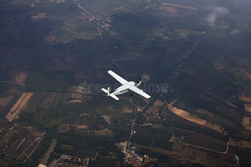 Un aeroplano sorvola il framland per il viaggio fotografia stock libera da diritti