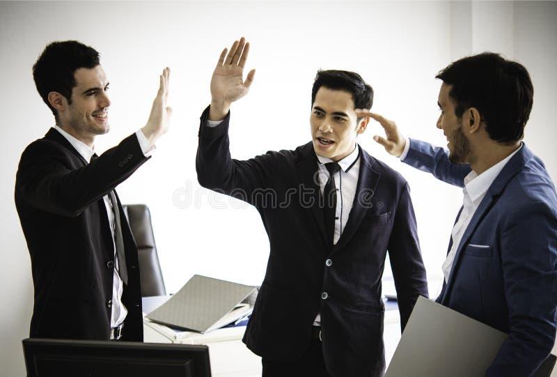 Un affare di tre giovani alto--cinque fa parte del gruppo, riuscita società fotografia stock