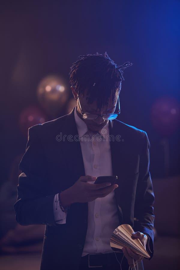 Un Africain charmant utilise un smartphone à la fête photos libres de droits