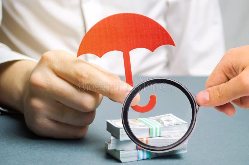 Un agent d'assurance tient un parapluie rouge au-dessus des billets d'un dollar Protection de l'épargne Maintenant l'argent sûr I photos libres de droits