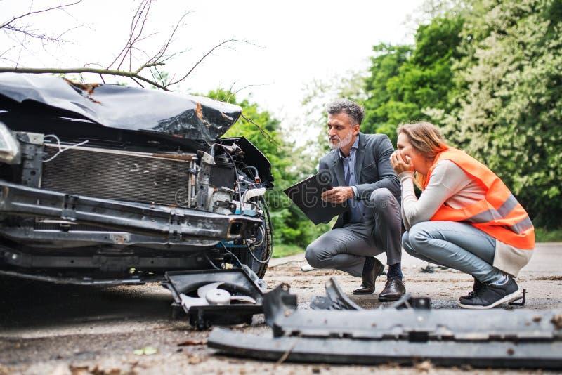 Un agente di assicurazione e un autista della donna che esaminano l'automobile sulla strada dopo un incidente immagini stock