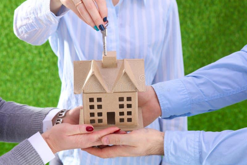 Un agente per la proprietà con una casa e una chiave fotografia stock libera da diritti